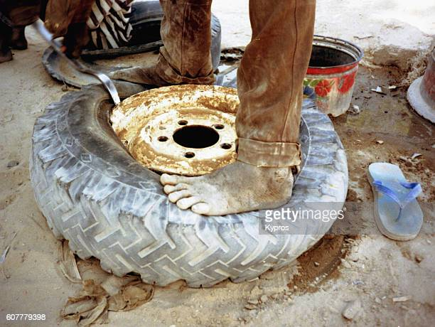 africa, north africa, sahara desert, tchad, lake chad area, view of barefoot man attempting to repair a punctured rubber tyre. after a hundred worthless african repairs, it became necessary to do the patching and glueing myself. the mentality was always t - puncturing stock pictures, royalty-free photos & images