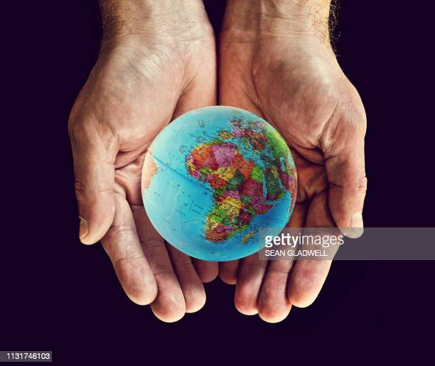 africa on globe in cupped hands - south africa stock pictures, royalty-free photos & images