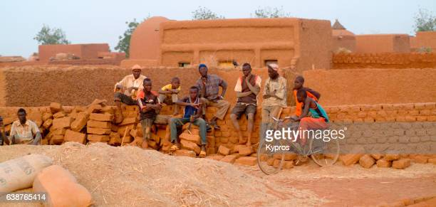 africa, sahara desert, north africa, niger, view of group of young men sitting on mud brick wall talking (year 2007) - human powered vehicle fotografías e imágenes de stock