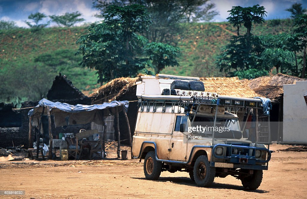 Africa, Southern Africa, Mozambique, View Of Safari Vehicle On Dirt Track In African Village (Year 2000) : Stock Photo