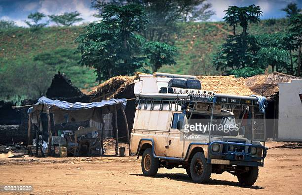 Africa, Southern Africa, Mozambique, View Of Safari Vehicle On Dirt Track In African Village (Year 2000)