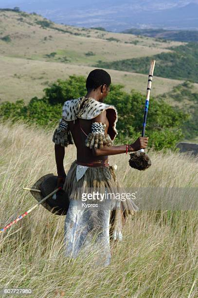 Africa, Southern Africa, South Africa, KwaZulu, Natal, Zululand, View Of Genuine African Zulu Warrior Standing In Long Grass On Mountain (Year 2009)