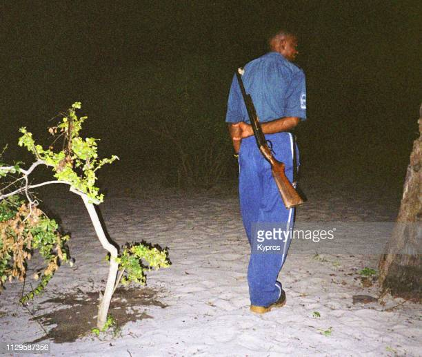 Africa, Tanzania, 2000: View Of African Security Guard Protecting White Mans Camp With Shotgun. On Beach At Night