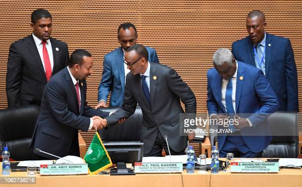 Africa Union Chairperson and the President of Rwanda Paul Kagame shakes hands with Ethiopia's Prime Minister Abiy Ahmed next to the Chairperson of...