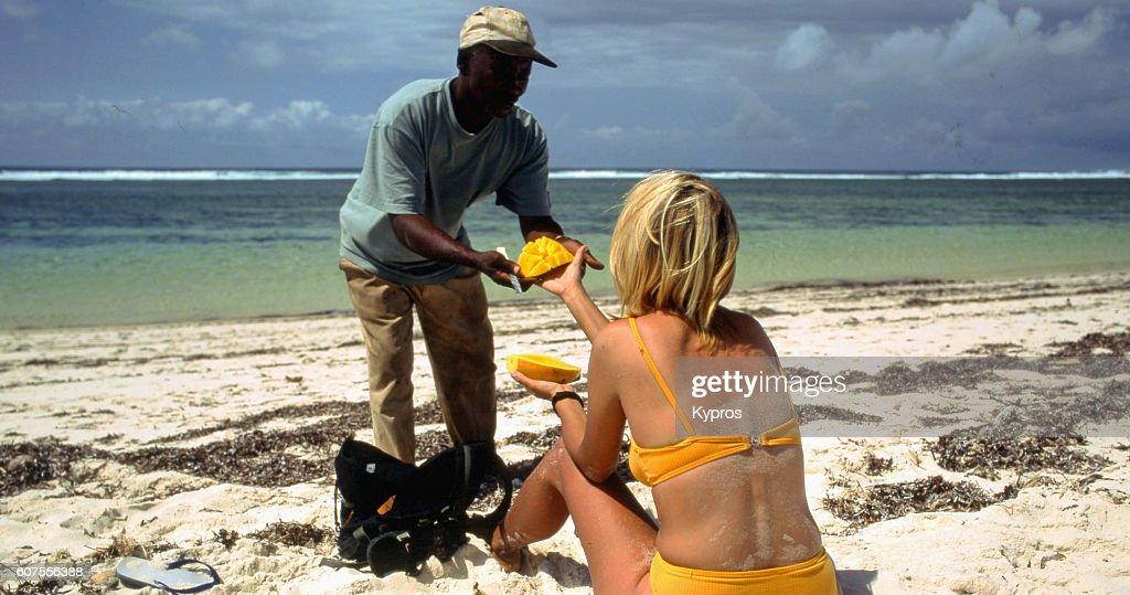 Africa, View Of Africa, East Africa, Kenya, View Of Caucasian Woman Wearing Bikini On Beach Buying Fruit (Year 2000) : Stock Photo