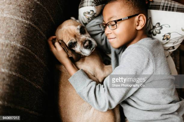 africaan america boy age 9 cuddled with dog - adoptie stockfoto's en -beelden