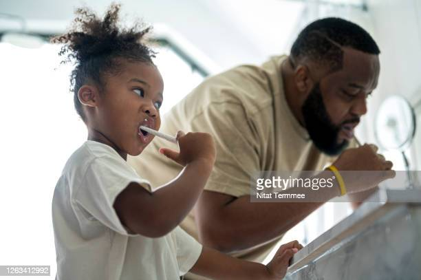 african adorable kindergarten age girls and father brushing teeth in bathroom at home. selective focus at a little girls missing a primary teeth. - single father stock pictures, royalty-free photos & images