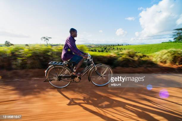 african adult male on a bicycle cycling in motion between tea plantations - between stock pictures, royalty-free photos & images