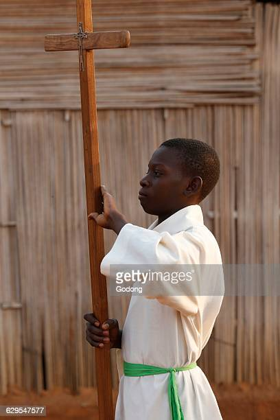 African altar boy carrying a cross