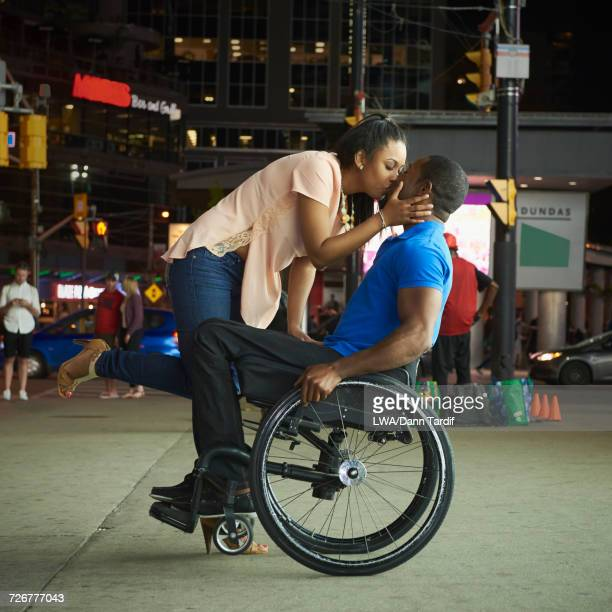 African America woman kissing man in wheelchair in city at night
