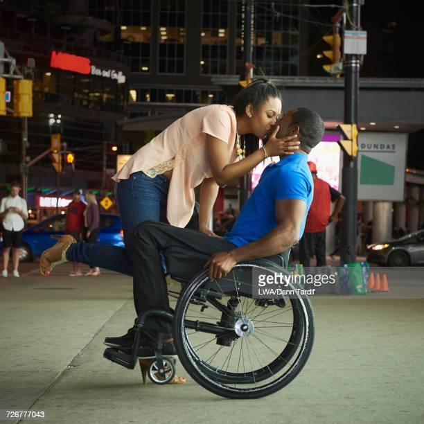 african america woman kissing man in wheelchair in city at night - pessoas com deficiência imagens e fotografias de stock