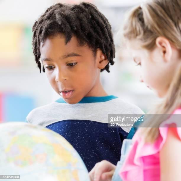 Afrikanisch-amerikanischen und kaukasischen Schüler studieren Globus
