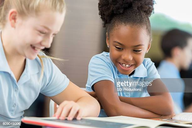African American and Caucasian schoolgirls laughing at a funny book