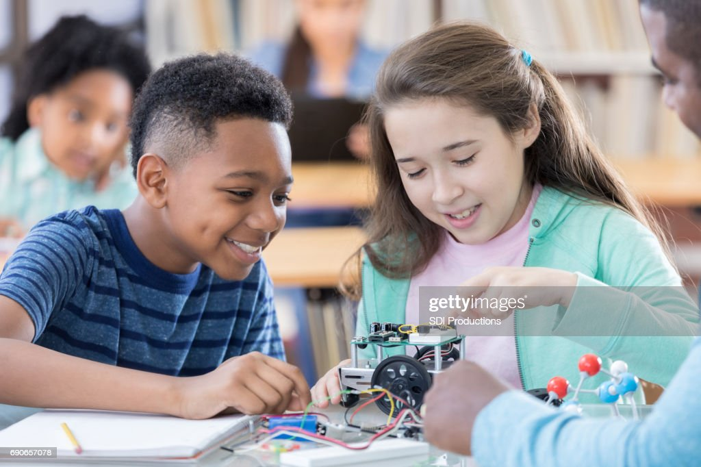 African American and Hispanic students build a robot together : Stock Photo