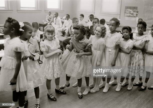 African American and white school girls standing in a classroom while boys sit behind them.