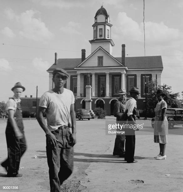 African American and whites outside a Southern City Hall with a statue of a Confederate soldier in front