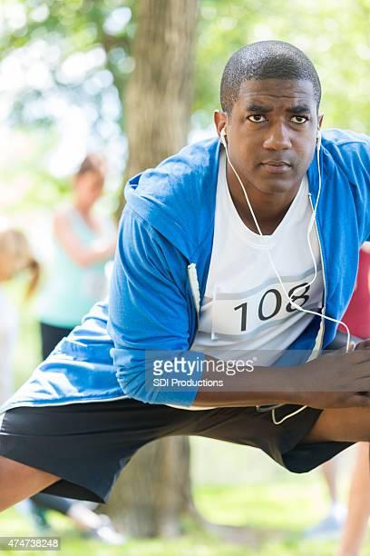 African American athlete stretching before running marathon race