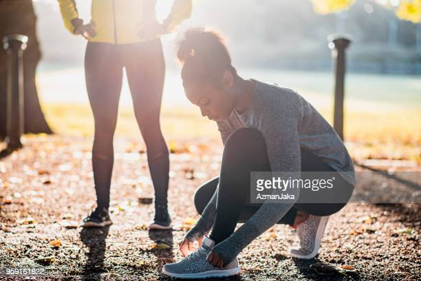 African American athlete tying her shoelaces before running