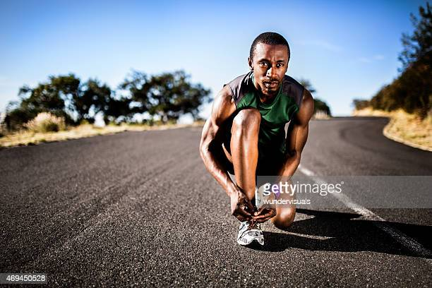 African American athlete tying his shoelaces ready for fitness t