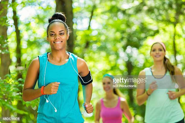 African American athletic woman smiling as she runs with friends