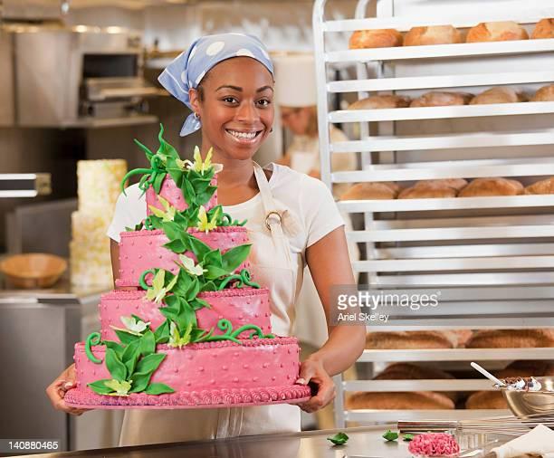 African American baker holding elaborate wedding cake in bakery