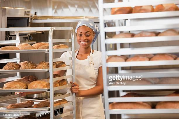 African American baker pushing bread cart in bakery