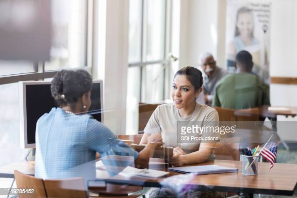 african american banker and hispanic soldier confer - incidental people stock pictures, royalty-free photos & images