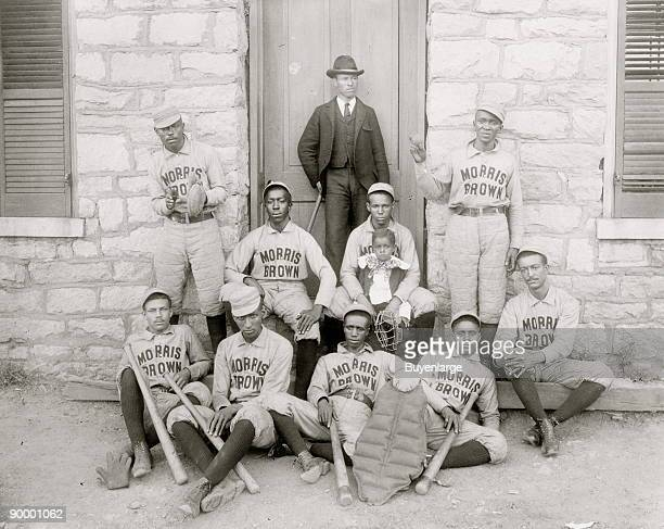 African American baseball players from Morris Brown College with boy and another man standing at door Atlanta Georgia