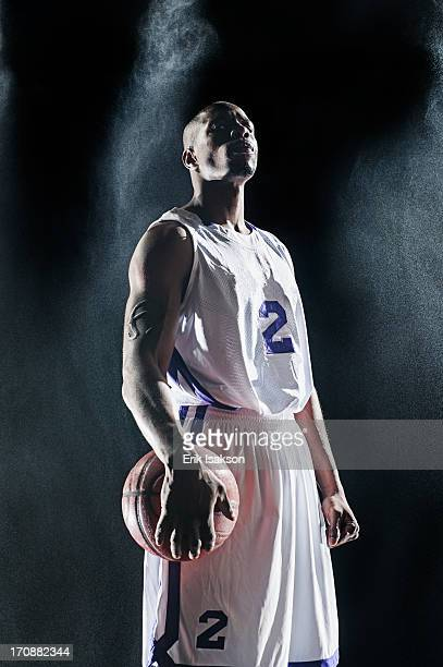 african american basketball player standing under lights - basketball player stock pictures, royalty-free photos & images
