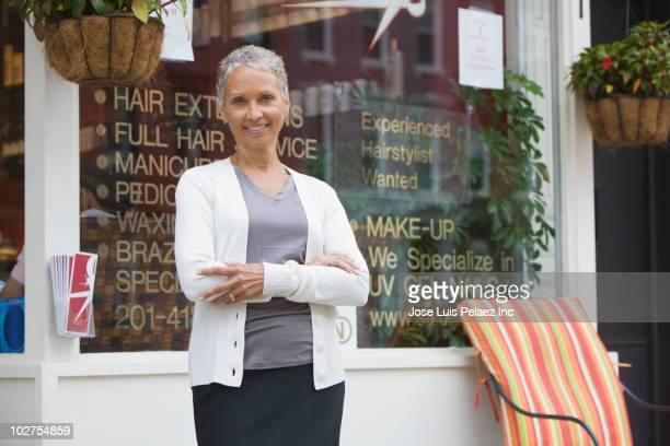 African American beauty salon owner standing outdoors