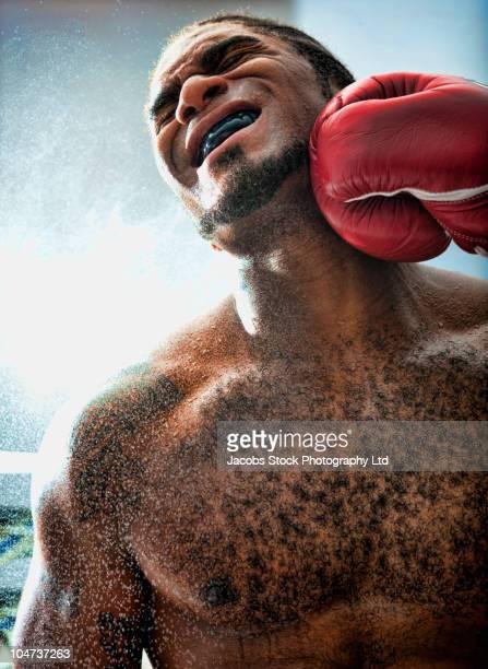 african american boxer getting hit - behaart stock-fotos und bilder