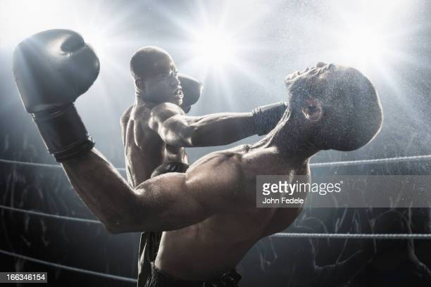 African American boxer hitting opponent in boxing ring
