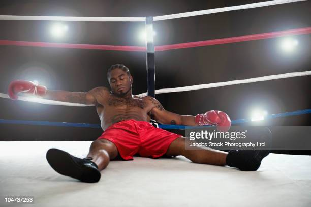 African American boxer laying in boxing ring