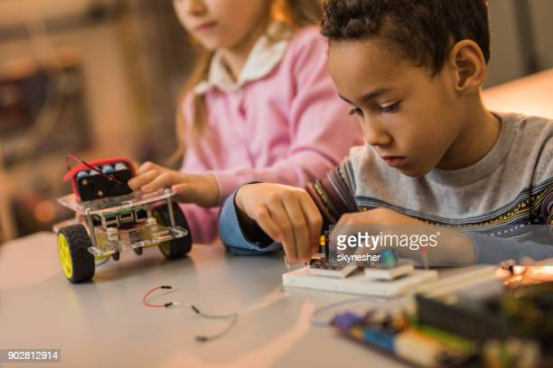 African American boy assembling electrical components of futuristic robot in laboratory.