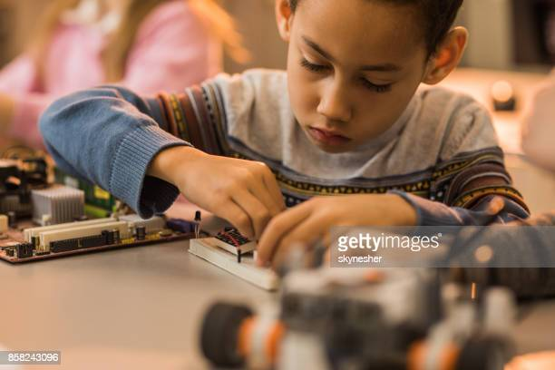African American boy assembling wires on a computer component.