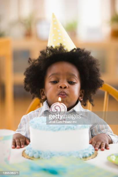 African American boy blowing out birthday candle