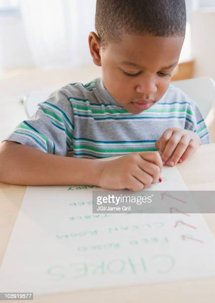 African American boy checking list of chores