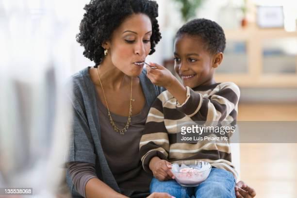 African American boy feeding mother ice cream