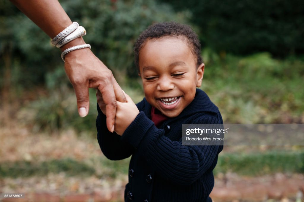 African American boy holding hand of mother in park : Stock Photo