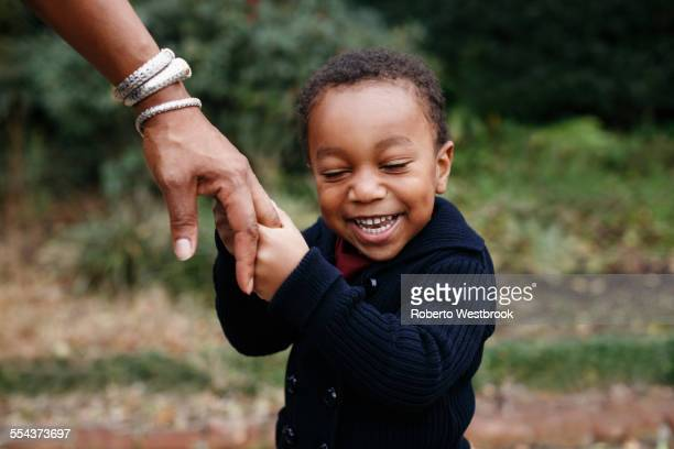 African American boy holding hand of mother in park