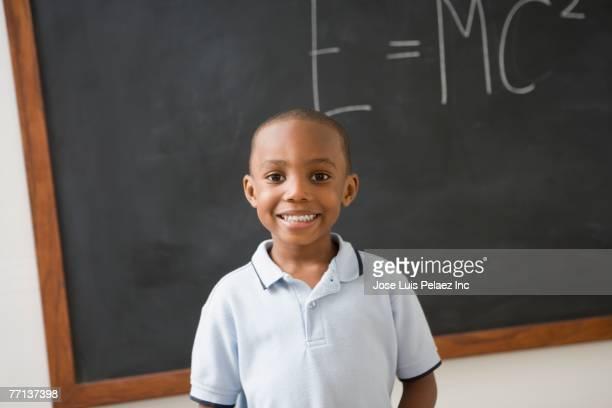 African American boy in front of black board