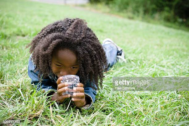 African American boy laying in grass and looking in jar