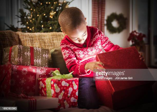 African American boy opening Christmas presents