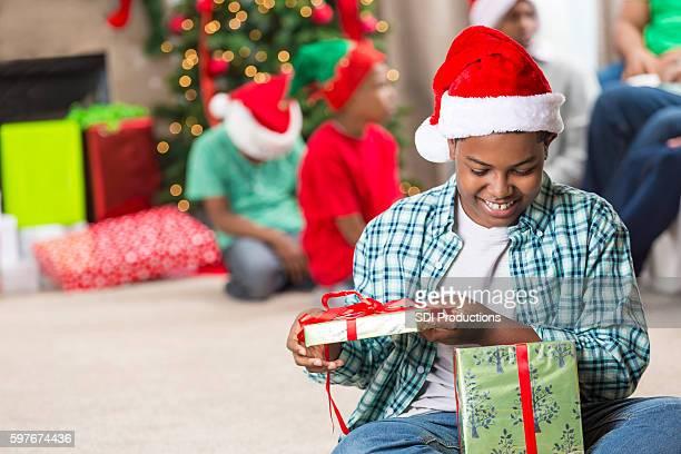 African American boy peeks inside Christmas gift