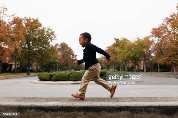African American boy playing on suburban street