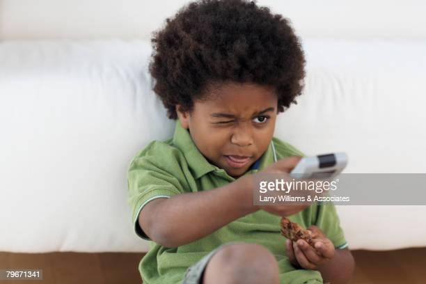 African American boy pointing remote control