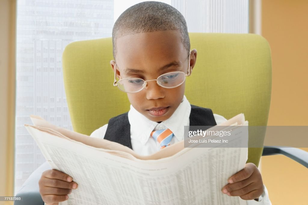 African American boy reading newspaper : Stock Photo