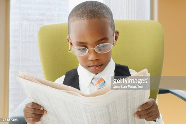 African American boy reading newspaper