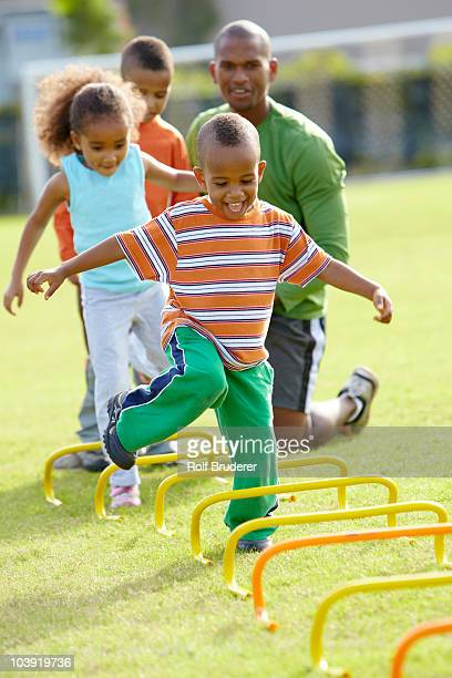 african american boy running across obstacle course - obstacle course stock pictures, royalty-free photos & images