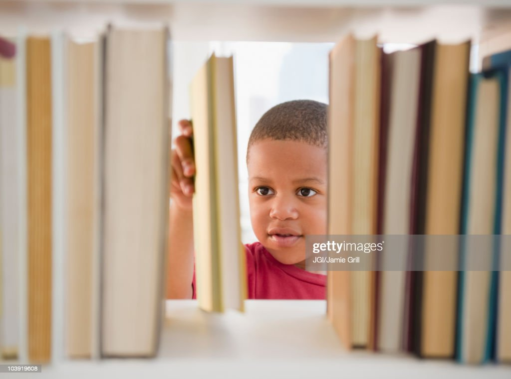 African American boy selecting book : Stock Photo